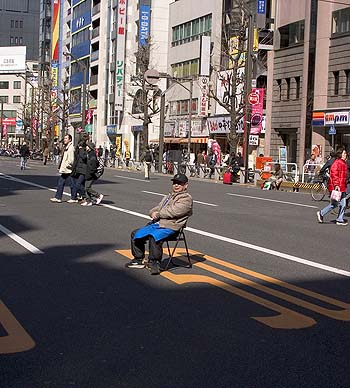 A man rests during Chuo Dori's pedestrian hours for a national holiday.