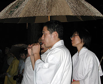 A priest plays the flute in the rain.